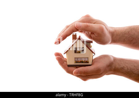 Home protection. Small house covered by hands isolated on white background with clipping path - Stock Image