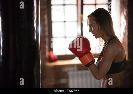 A woman in boxers gloves standing in the gym - Stock Image