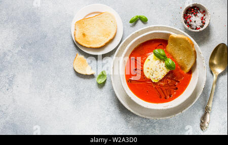 Tomato soup with mozzarella cheese, Basil and spices in a white plate. A thick, hearty dish, served with bread toast and olive oil. Selective focus, c - Stock Image