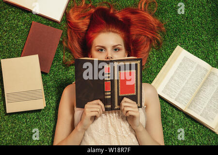 Red-haired girl lying on grass and looks from behind the book - Stock Image