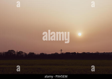 Sunset with sand suspended in the atmosphere, coluring the sky red, over some fields and hills - Stock Image