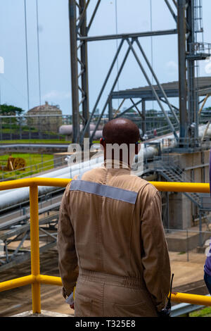 An oil worker looks out over the Punta Europa oil and gas complex in Equatorial Guinea - Stock Image