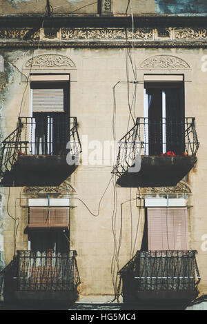 Close-up view of facade with balconies and four windows with closed and opened jalousie, old house in touristic - Stock Image