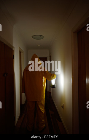 Man in corridor with lantern wearing wet weather gear - Stock Image