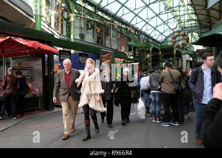 People visiting Borough Market at Christmas time strolling inside past stalls in Southwark South London England UK  KATHY DEWITT - Stock Image