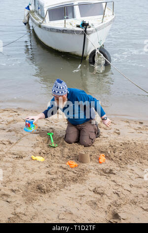 Bearded man with child's bucket and spade building sandcastles on the beach at Conwy (Conway), North Wales for children - Stock Image