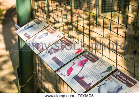 Poznan, Poland - April 18, 2019: Row information boards by a grid cage with birds in the old zoo. - Stock Image