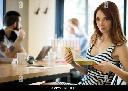 Woman reading book in cafe, portrait - Stock Image