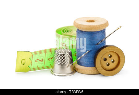 Spool of blue thread, needle, button, measuring tape and thimble isolated on white - Stock Image