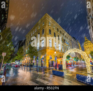 Budapest, Hungary - Snowy evening and Christmas market gate at the Zrinyi and Oktober 6 street corner with St.Stephen's Basilica at background - Stock Image