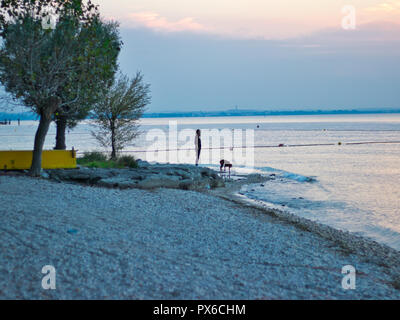 Woman at the beach during sunset - Stock Image