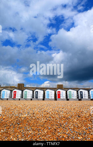 A line of 12 new Beach huts running through the centre of the image with red, blue and green doors and balconies, below is a yellow pebble beach and a - Stock Image