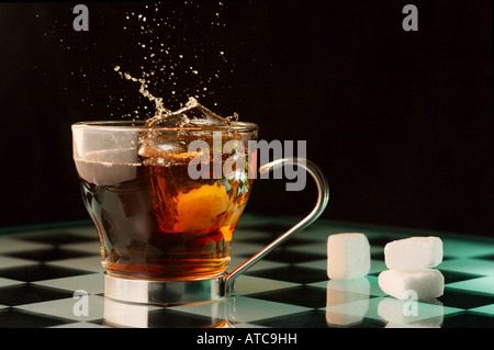 A sugar cube being dropped into a cup of tea. - Stock Image