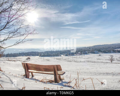 Winter landscape, sunny day. Footprints in the fresh snow lead to a wooden bench - Stock Image