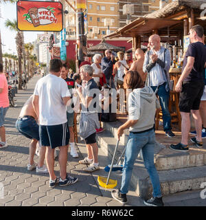 Benidorm, Costa Blanca, Spain. Drinkers enjoy temperatures at the Tiki Beach bar on Levante beach which is flagged to be closing soon. - Stock Image