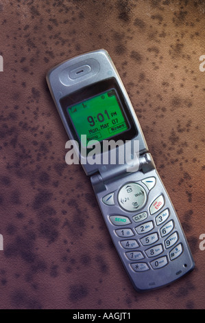 A cell phone on a barren, brown background displays 9:01  p.m. - Stock Image
