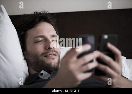 Man reclining in bed looking at two smart phones - Stock Image