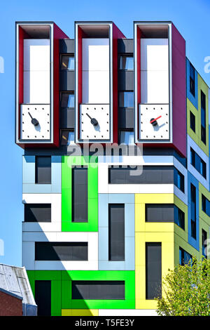 Clock hands on  unusual tall clock tower on top of colourful modern architecture purpose built student accommodation flats colour geometric pattern UK - Stock Image