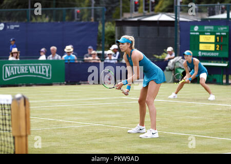 British tennis players Katie Boulter (foreground) and Katie Swan (background) await their opponent's serve during a women's doubles match at a professional grass court tournament in the United Kingdom. Boulter and Swan played together in matching outfits. - Stock Image
