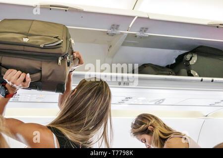 Cartagena Colombia Rafael Nunez International Airport CTG Avianca flight AV 34 onboard cabin Hispanic overhead luggage bin woman storing bag - Stock Image