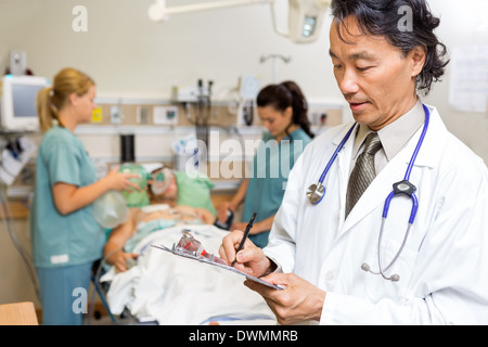 Doctor Writing Notes in Emergency - Stock Image