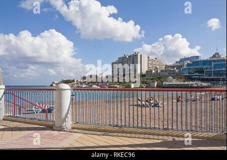 St. George's Bay, San Ġiljan, Malta a sheltered sandy beach near Valetta, sunbathing in november on a sunny day - Stock Image
