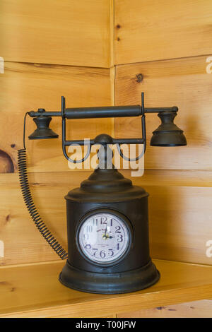 Black decorative metal antique telephone with integrated clock face on pinewood shelf in basement inside piece sur piece Eastern white pine log home - Stock Image