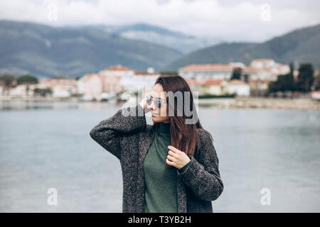 Beautiful young trendy girl in sunglasses walks near the shore and looks into the distance. - Stock Image