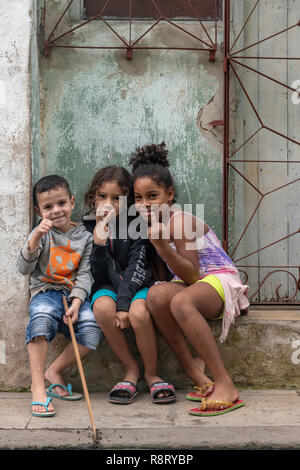 Three cheeky Cuban children, a boy and two girls sat on a doorstep in Havana Cuba - Stock Image