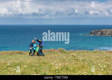 A family of holidaymakers taking a selfie with a mobile phone standing on the North Cornwall Coast. - Stock Image