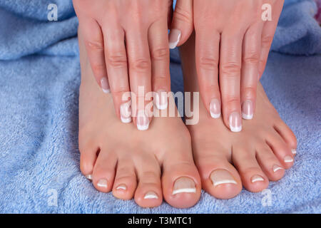 Pedicure and manicure girl feet and hands on blue towel in beauty and spa studio. Woman french nails polish concept. Close up, selective focus - Stock Image