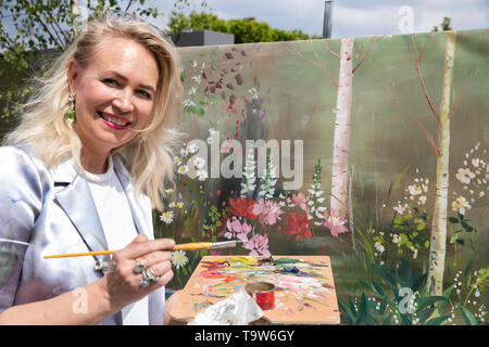 London, UK. 20th May, 2019. A female artist at work at the RHS Chelsea Flower Show Press Day which takes place before it officially opens tomorrow until Saturday 25th May. The world renowned flower show is a glamourous, fun and an educational day out which is attended by many celebrities. There are many gardens, floral displays, Marquees all set in the glorious grounds of The Royal Hospital Chelsea. Credit: Keith Larby/Alamy Live News - Stock Image
