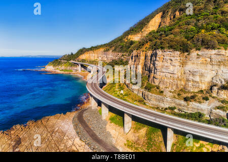 Sea cliff bridge section of the Grand Pacific drive around steep sandstone cliff at the edge of Pacific coast on a sunny day against blue sky in eleva - Stock Image
