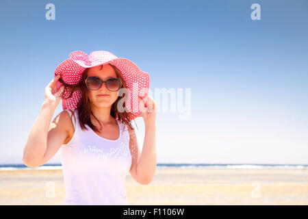 Woman in a pink hat on the sunny beach - Stock Image