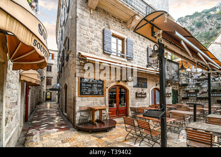 An outdoor cafe sits empty in the early morning in the tourist center of the medieval walled city of Kotor, Montenegro - Stock Image