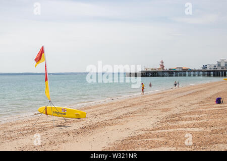 A lifeguard flag and surfboard on a British beach Southsea, Hampshire, UK - Stock Image