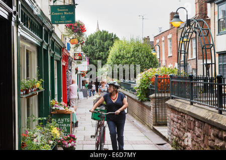 Mature woman pushing her bicycle past shops in Taunton. - Stock Image