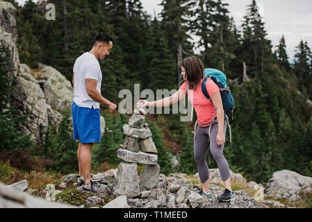Couple hiking, stacking rocks - Stock Image