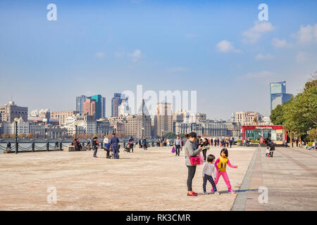 1 December 2018: Shanghai, China - Visitors on the bank of the Huangpu River on the Pudong side, opposite The Bund, Shanghai. - Stock Image