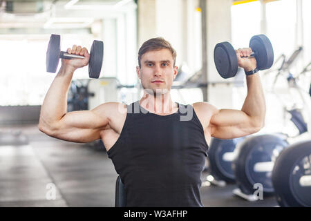 Closeup portrait of young adult man muscular built handsome athlete working out in a gym, sitting and holding two dumbbell with raised arms, swing sho - Stock Image