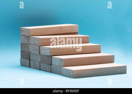 Close-up Of Wooden Building Block Stacked Over Blue Backdrop - Stock Image