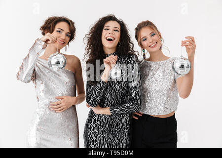Image of a beautiful young happy women friends posing isolated over white wall background holding little disco balls on a party. - Stock Image