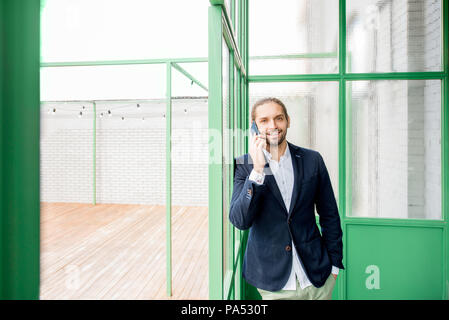 Businessman talking phone standing indoors in the beautiful green hall with glass partitions, wide angle view - Stock Image