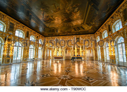 An ornate golden interior ballroom with a grand piano inside the Rococo Catherine Palace at Pushkin near St. Petersburg, Russia. - Stock Image