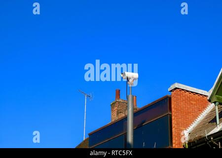 Big Brother is watching you. CCTV camera high above the rooftops in Ipswich, Suffolk, UK. February 2019. - Stock Image