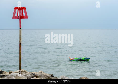 A man enjoying hot weather in an inflatable boat along Highcliffe beach in Dorset, England, UK. - Stock Image