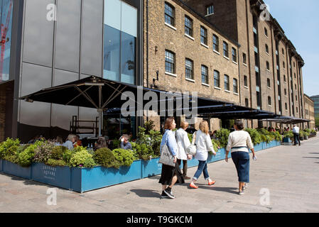 People walking past Granary Square Resturant in Granary Square, Kings Cross, London England Britain UK - Stock Image