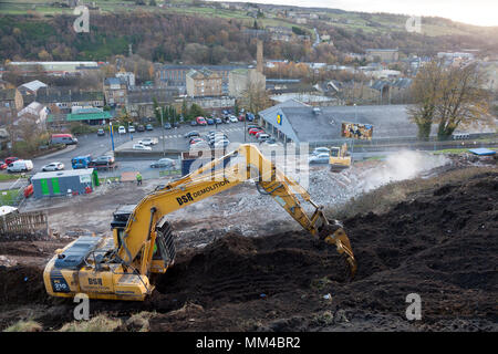 Digger at work levelling ground for redevelopment, Sowerby Bridge, West Yorkshire - Stock Image