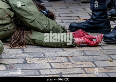 violence against people battered woman's hands in the blood next to a man in military shoes. - Stock Image