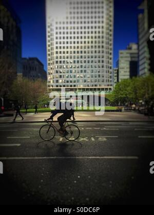 Cyclist passing no.1 Canada Square, Docklands, Canary Wharf, London. Dramatic lighting, reflecting from glass and - Stock Image
